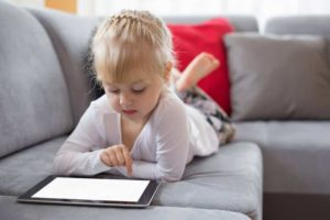 picture of a girl lying on the couch with a tablet