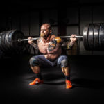 man squatting with weighted barbell
